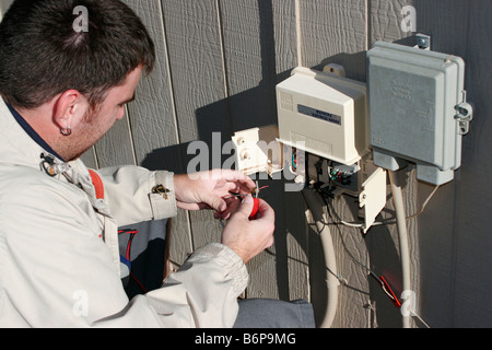 A telephone repairman fixes the faulty wiring on a residential communication service - Stock Photo