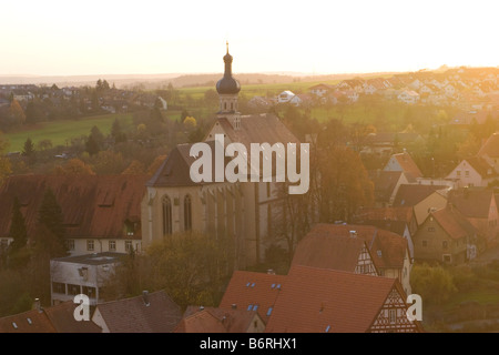 The sun sets over the ancient streets of the Neckar Valley town of Bad Wimpfen and its Catholic Church - Stock Photo