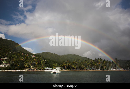 A rainbow appears over a sailing boar moored in Marigot Bay, St Lucia, Windward Islands, Caribbean in the West Indies. - Stock Photo
