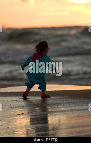 Little girl walking on beach with large waves in background - Stock Photo