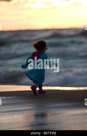 Little girl dressed in colorful clothes walking on beach - Stock Photo