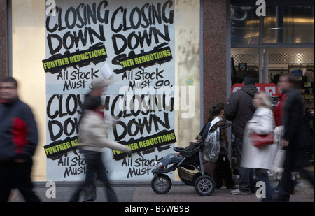 shoppers and families walking past closing down sale signs in a shop window in the uk - Stock Photo