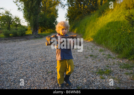 A boy carrying logs - Stock Photo