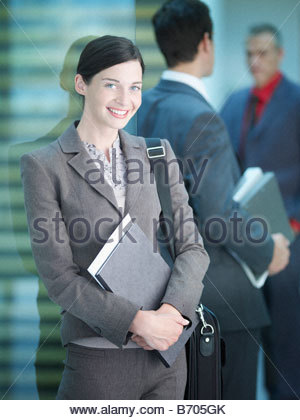 Businessman holding paperwork and briefcase - Stock Photo