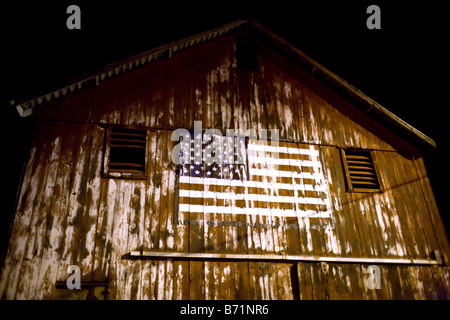 An American flag painted on an old barn - Stock Photo