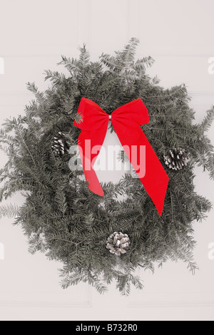 A Christmas wreath hanging on the white front door of a home Red bow - Stock Photo
