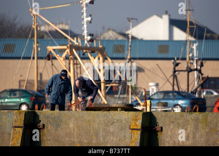 two fishermen repairing fishing nets on harbour wall county down Northern Ireland UK - Stock Photo
