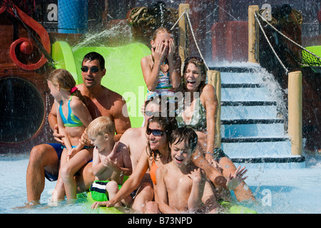 Portrait of family enjoying on waterslide in water park - Stock Photo