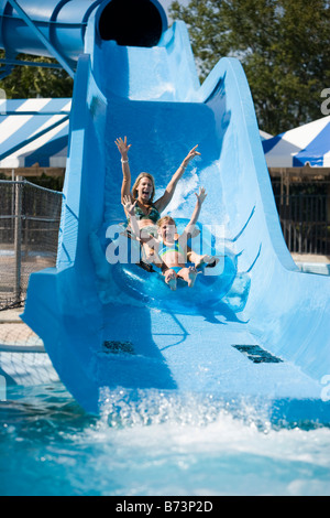 Mother and daughter sliding on water slide in water park - Stock Photo