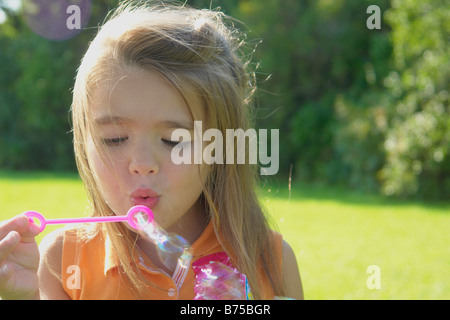 Six year old girl blowing bubbles in park, Winnipeg, Canada - Stock Photo