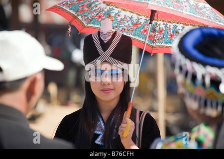 A Hmong girl wearing sunglasses, with reflections of other participants, during a Hmong New Year Ceremony Ball tossing - Stock Photo