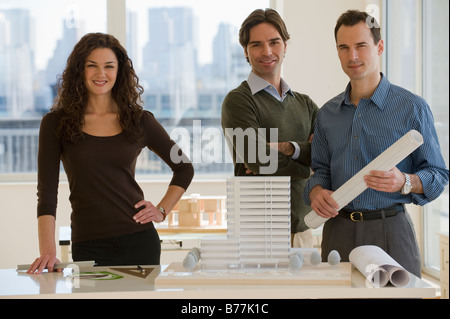 Portrait of architects building model and blueprints - Stock Photo