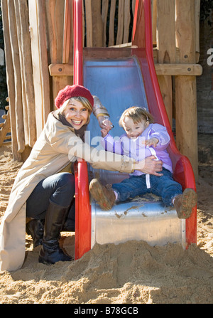 Mother and her 2-year-old daughter on a slide, playground, Zurich, Switzerland, Europe - Stock Photo