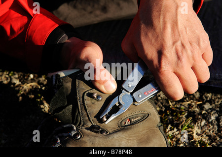 Trekker reparing his mountaineering boot with Leatherman tool, Ikasartivaq-Fjord, East-Greenland, Greenland - Stock Photo