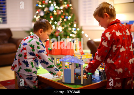 Two young boys playing with toys by Christmas Tree - Stock Photo