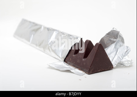 Triangular shaped dark chocolate bar in silver foil - Stock Photo