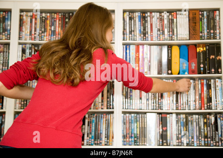A girl choosing a DVD from a large collection of DVDs, UK - Stock Photo