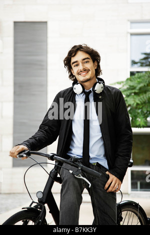 Man on a bicycle, headphones on - Stock Photo