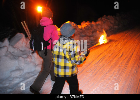 adult woman and young boy walking uphil on snowy track lit by torchlight - Stock Photo