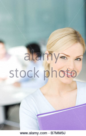 A businesswoman in an office, two colleagues in background having a discussion - Stock Photo