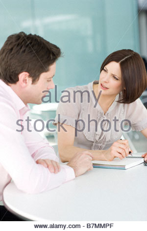 Two business colleagues having a discussion in an office - Stock Photo