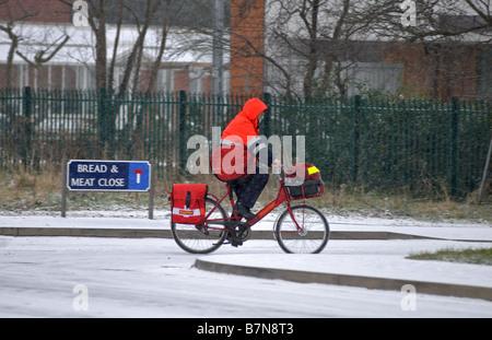 Postman on bike in snow, Warwick, Warwickshire, England, UK - Stock Photo