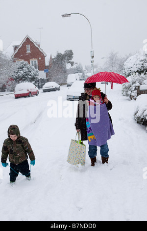 A mother walks through the snow with her two children in Muswell Hill north London on the 2nd of February 2009 - Stock Photo
