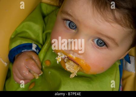 A baby girl feeding herself . - Stock Photo