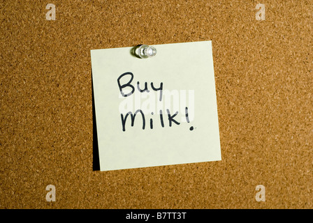 Post it note or memo on a cork board that says buy milk. - Stock Photo