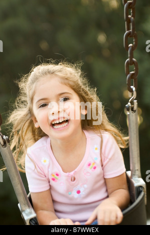 little girl playing on swing laughing - Stock Photo