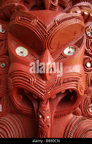 A Maori carving of a face with the tongue sticking out and eyes wide open on a marae meeting hall in Waitangi Treaty - Stock Photo