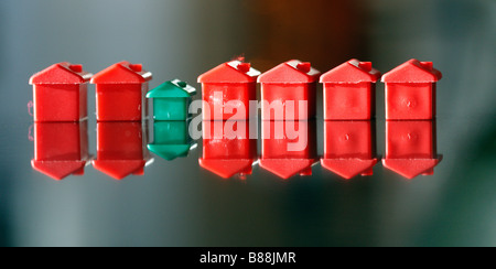 Row of small plastic model houses and hotels, from a popular board game. - Stock Photo