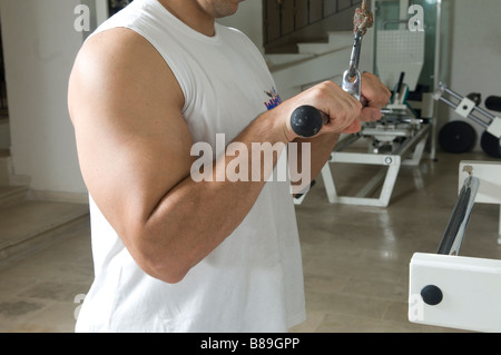 Man doing triceps cable pull down exercise in the gym - Stock Photo
