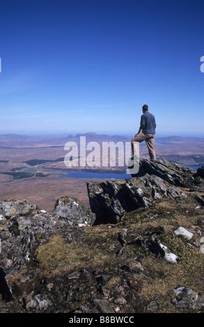 Hillwalker standing near summit of Ben Klibreck munro looking North towards Altnaharra Loch Naver Sutherland Scotland - Stock Photo