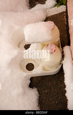 Two pints of milk in glass bottles delivered to the doorstep in snowy conditions - Stock Photo