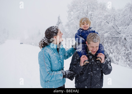 Couple take young son for an outdoor walk during Winter in Pedro Bay, Alaska. - Stock Photo