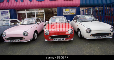 Row of Retro Nissan Figaro cars for sale at car dealers - Stock Photo