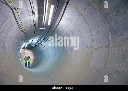 Engineers inspect access adit to main power cable tunnel in London, lined with concrete supporting segments. - Stock Photo