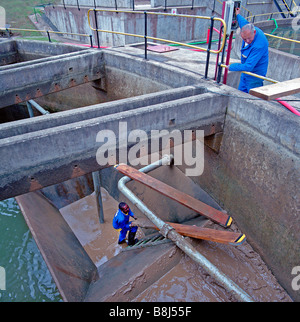 Workers cleaning sludge from a settlement reservoir at a water treatment plant in South Africa. - Stock Photo