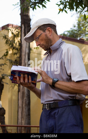 India Tamil Nadu Madurai lost foreign tourist looking at Lonely Planet guide book - Stock Photo