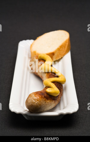 german Thuringer Bratwurst with mustard and slice of bread on serving dish, placed on black textile background, - Stock Photo