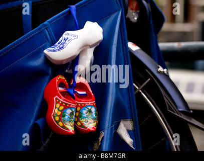 souvenir clogs hanging on back of a bicycle in Amsterdam - Stock Photo