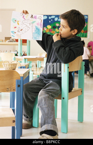 Boy holding up drawing in class room - Stock Photo