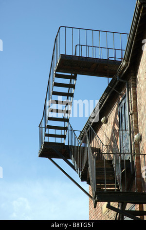 External fire escape, metal steps to roof safety against a blue sky - Stock Photo
