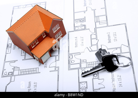 A model home and house key on architectural floor plans for an extension - Stock Photo