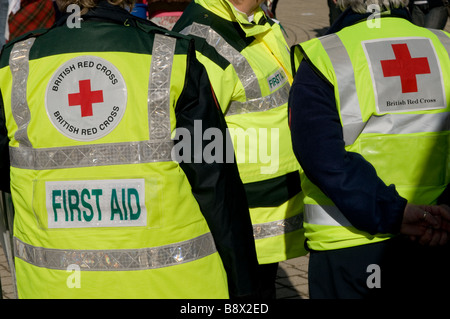 rear view of three First aid volunteer British Red Cross workers wearing high visibility yellow jackets, UK - Stock Photo