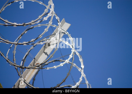Coils of razor wire against blue sky with galvanised steel support bracket - Stock Photo