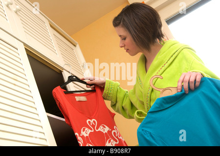 Young woman / teenager in bedroom choosing clothes / outfit to wear - Stock Photo