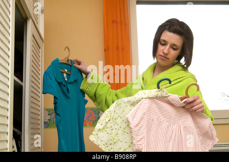 Woman in bedroom choosing the right clothes - Stock Photo