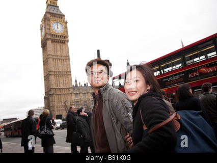 Asian oriental tourist couple in 20s / 30s visiting London, on street in front of Big Ben and London double decker - Stock Photo